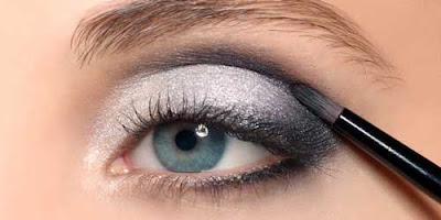 maquillando los ojos con sombras oscuras