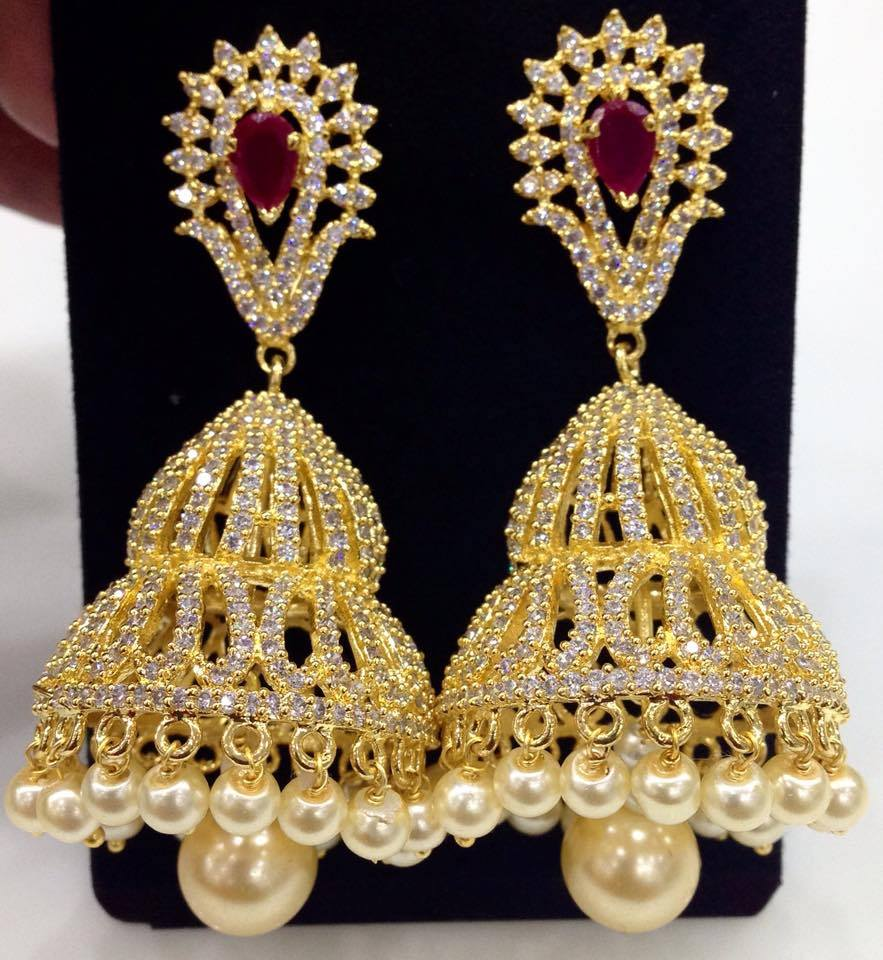 In The Crowd Wearing This Pair Of Golden Cz Stone And Ruby Jumkas These Are Durable Skin Friendly Wear Earrings With A Matching Saree