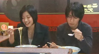 Misaki eats with a smile while Nakamura looks somber.
