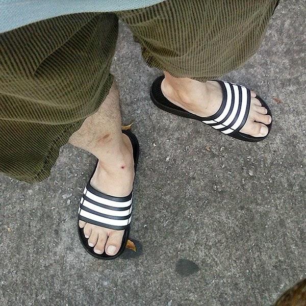 Foto de homem usando chinelos adidas duramo - Pés Masculinos