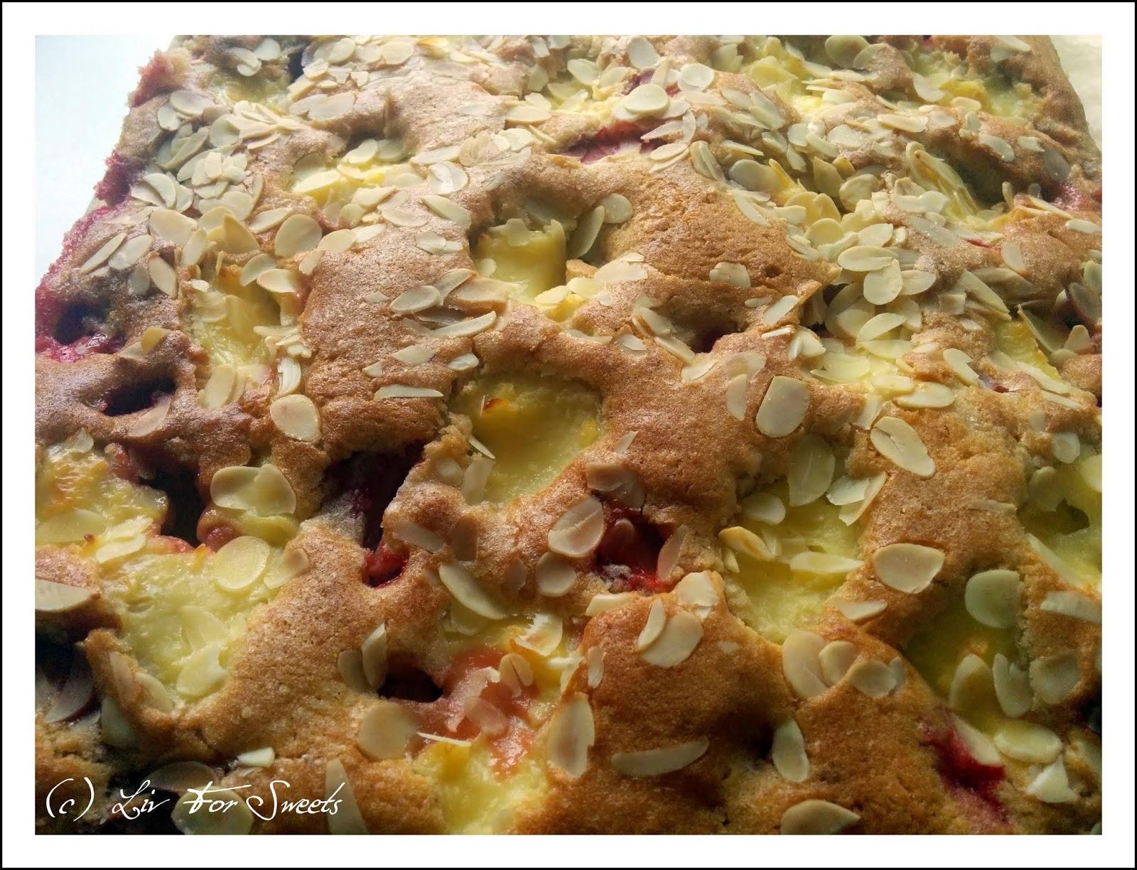 Der fertige Erdbeer-Butterkuchen mit Flecken aus Vanillepudding bestreut mit Mandelblättchen nach einem Rezept aus der Lecker Bakery