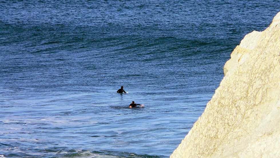 surfista remontando hacia el pico sopela