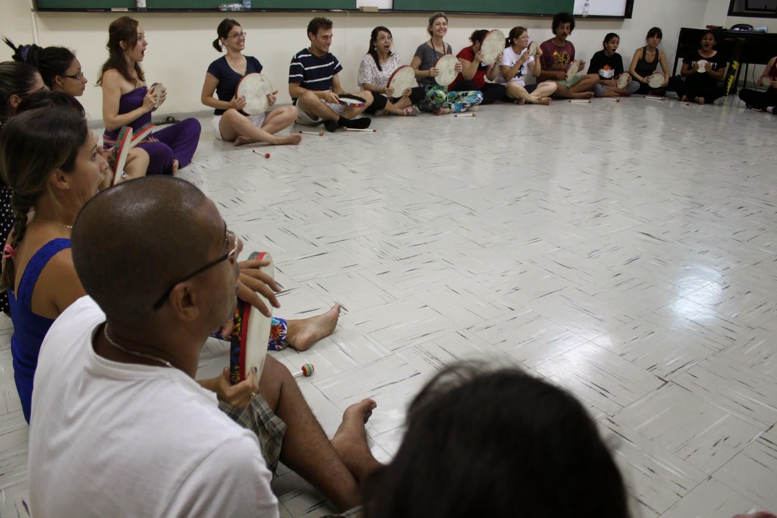 Descrição da Foto: Participantes estão em semi-círculo segurando o tambor com as mãos, sentados de pernas cruzadas.