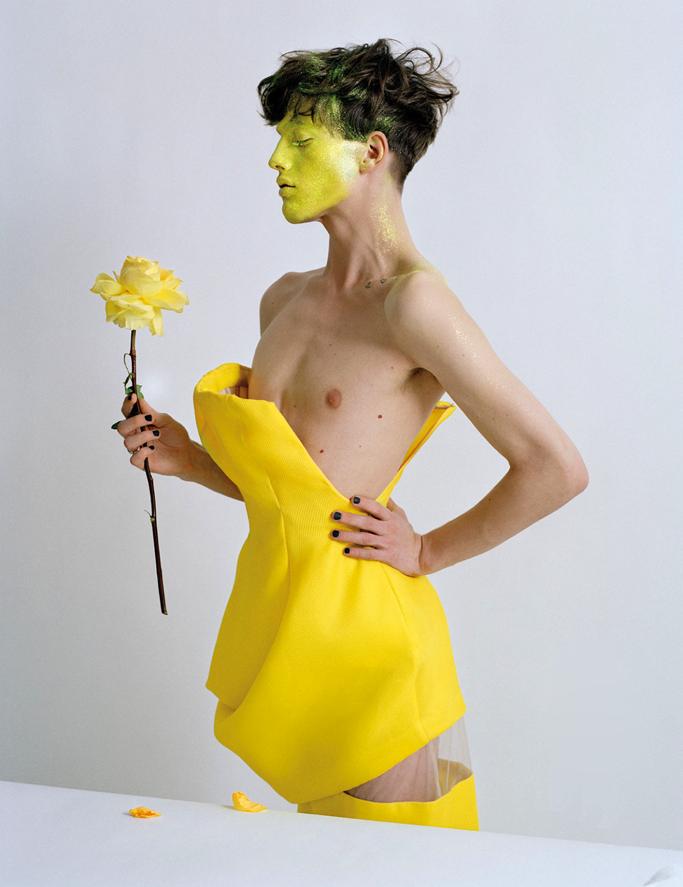 man in dress holding flower