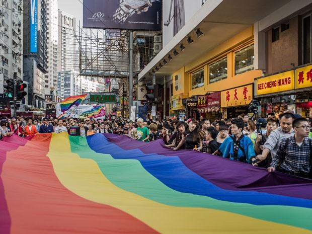 Participantes carregam bandeira em parada do orgulho de lésbicas, gays, bissexuais, travestis e transexuais realizada neste sábado (10) nas ruas de Hong Kong. Manifestantes marcham na busca pelos direitos iguais (Foto: AFP/ Philippe Lopez)