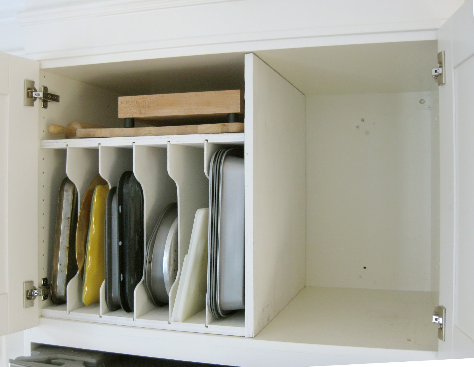 organizing trays in cabinet above refrigerator