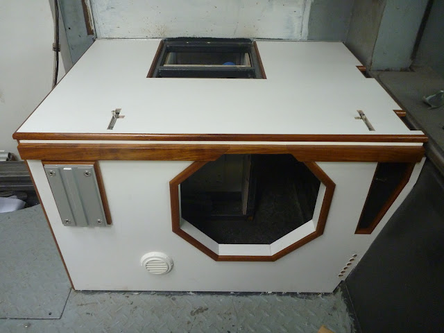 Nearside bench seat with rail for supporting a bed base, a cut-out for a subwoofer, an outlet for an Eberspacher heater, and a mounting plate for a Lagun table