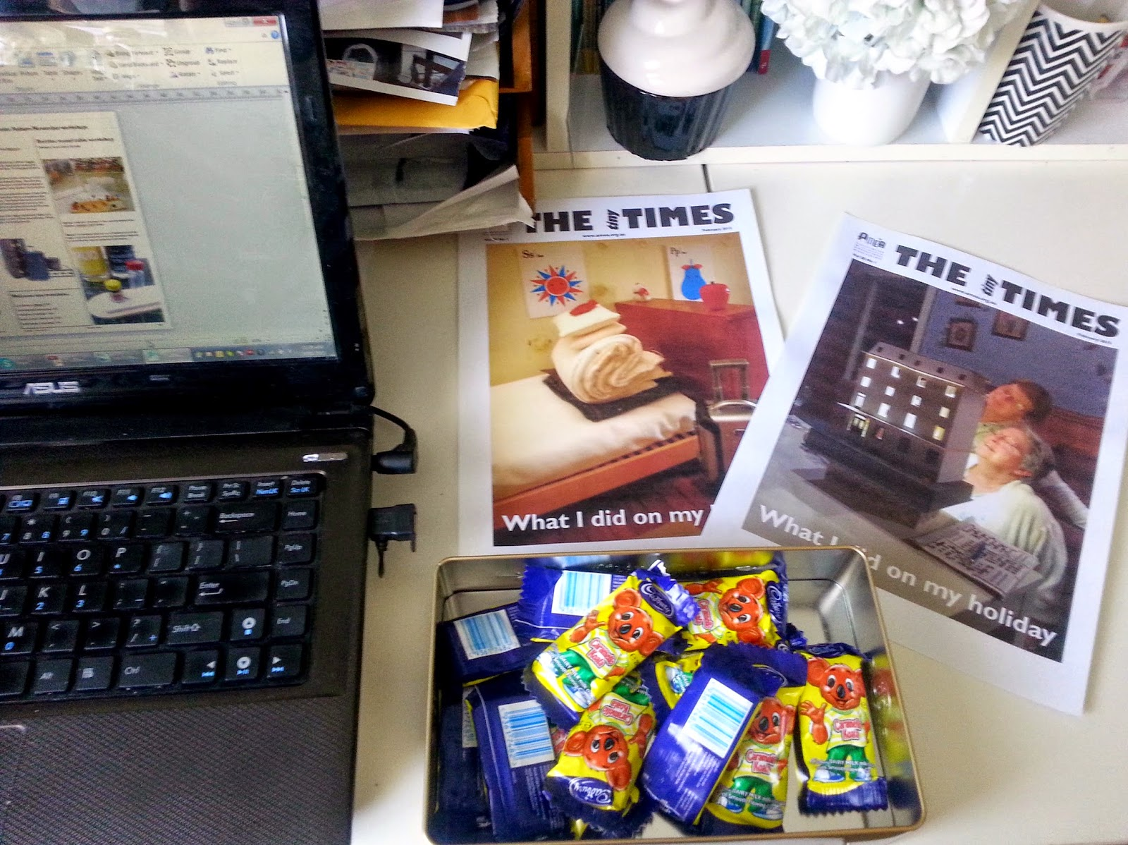 Laptop computer, a tin of Caramello Koalas and two sample covers of The tiny Times on a desk.
