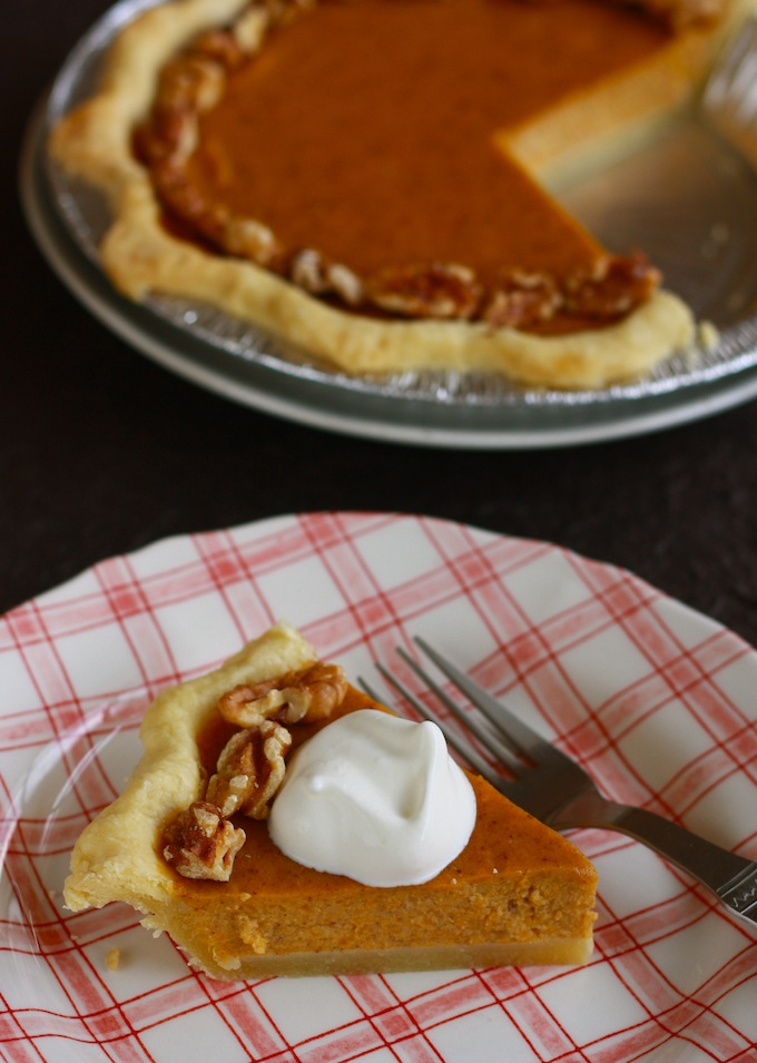 a slice of fresh pumpkin pie with sugarless whipped cream on top