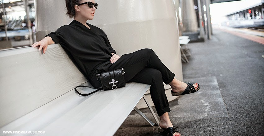 Mandi of Find Me A Muse fashion blog at Southern Cross Station in Melbourne sitting on bench wearing ASOS black jumpsuit Givenchy Obsedia quilted leather bag Tony Bianco Indiana slides Celine catseye sunglasses
