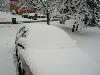 Car is covered in snow. Neither sheet nor windshield are visible.