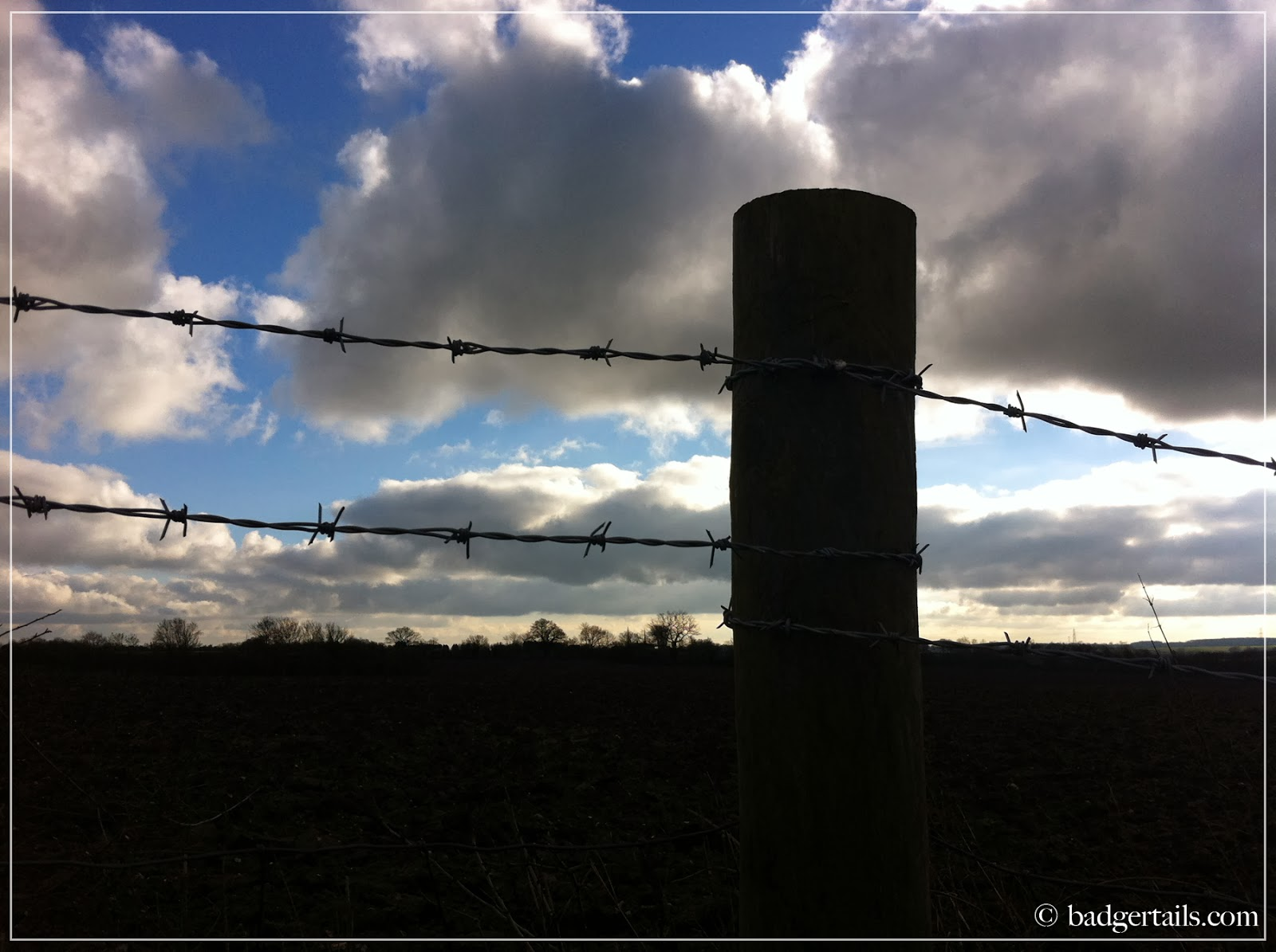 barbed wire fence with stormy sunny sky dramatic sky silhouette