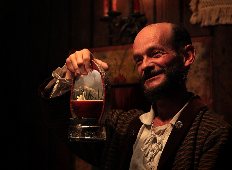 Actor sorridente mostrando um cisne em miniatura