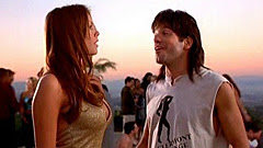 Nikki Cox in profile in a tight gold top as the Beer Girl with the sun setting behind her and David Cross as Ronnie in Run Ronnie Run movieloversreviews.filminspector.com