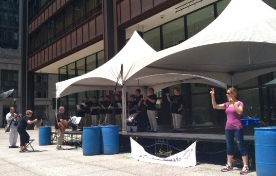 stage in Daley Plaza Chicago, covered with tent. Performers on stage. Sign Language Interpreter standing in front of stage.