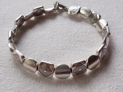 pulsera artesanal de abalorios plateados con dibujo en forma de rombo  y abalorios en forma de ovalo y con cierre mosquetón
