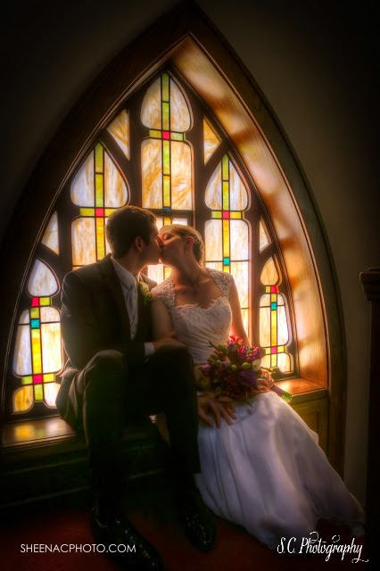Bride and groom kiss in front of stained glass window