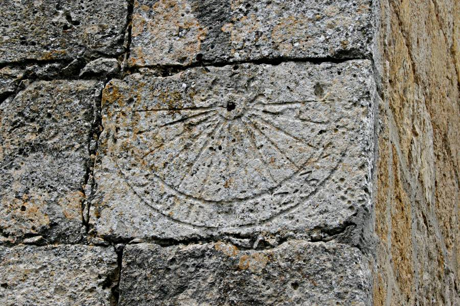 remains of sundial on a stone wall