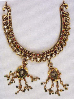 Mukut, ca. 19th cent. AD, Jaipur  The mukut, a crown-like head ornament, is mentioned in Sanskrit texts. Here, set in kundan and rubies, it has been inverted as a necklace, with two delicate pendants fringed with Basra pearls.