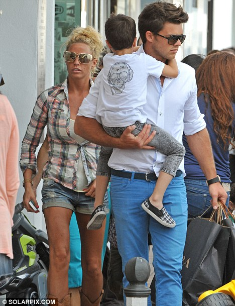 Now Leandro takes a turn carrying Peter Andre's son Junior as he and Katie go shopping