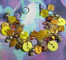 Charm bracelet has clusters of beads and buttons in sunshine yellow with silver charms