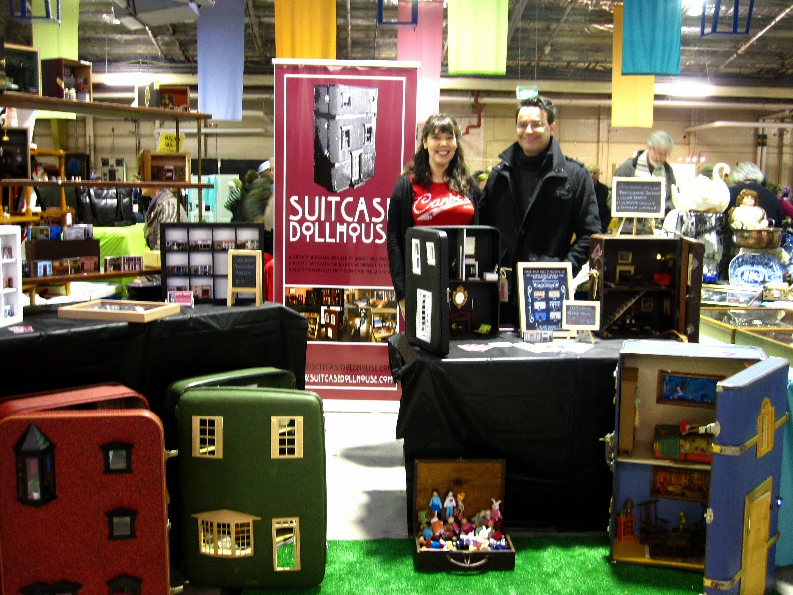 The Suitcase Dollhouse stall at the Old Bus Depot Markets at Kingston, with owners Marisa and David next to their banner.