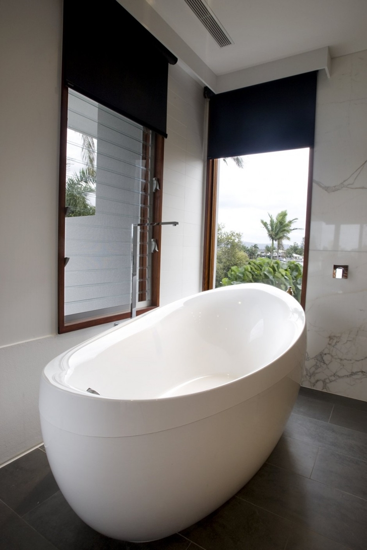 White bathtub in Modern house at Amalfi Drive by BGD Architects