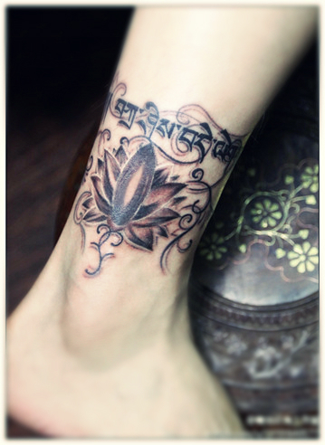 A well designed lotus flower tattoo along with some sanskrit characters