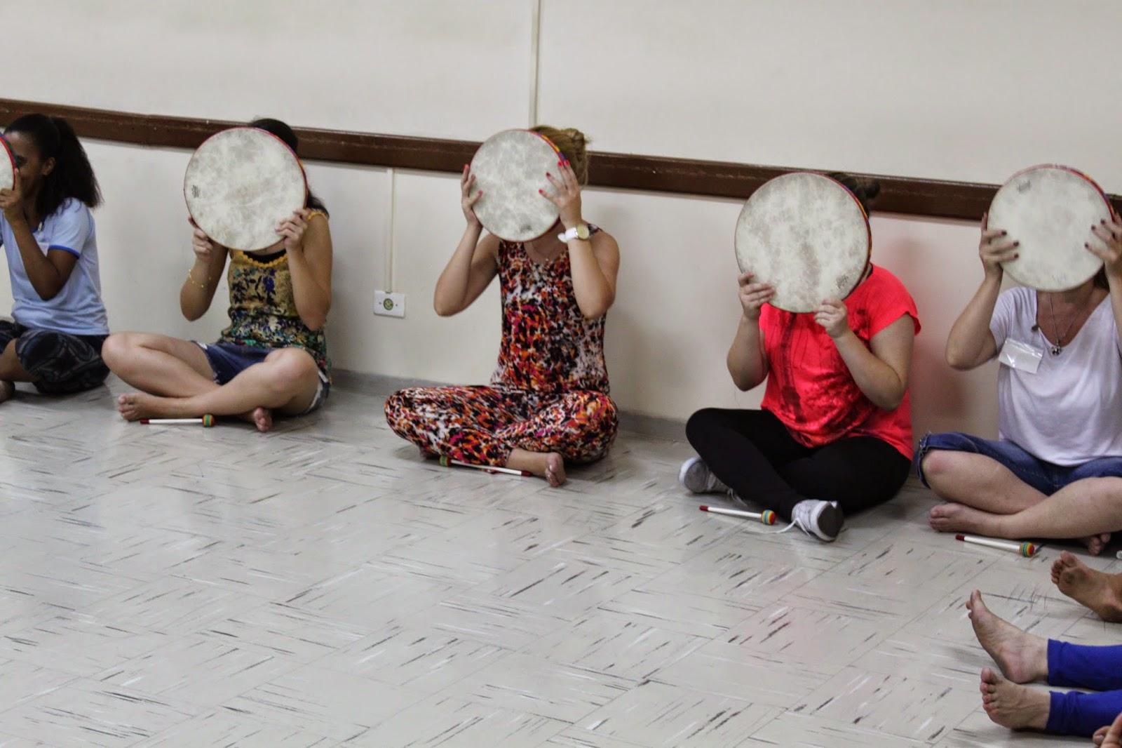 Descrição da Foto: Participantes estão em círculo, sentados de pernas cruzadas, segurando o tambor na frente do rosto.