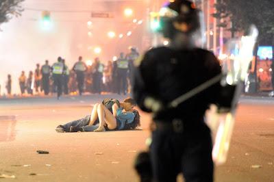 pareja de jovenes besándose en medio de la violencia de los disturbios en vancouver canada