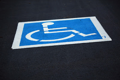 Free Freshly Painted Handicap Wheelchair Parking Sign in Parking Lot Creative Commons