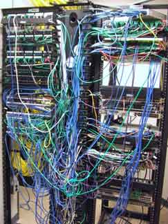 Rack of equipment entangled in a messy mass of cables