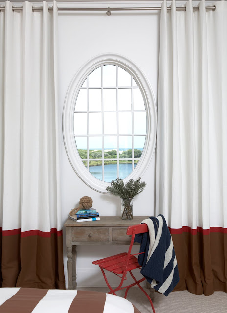 desk in a beach house with an oval mirror, white drapes with a single brown and red stripe on the bottom with a red metal beach chair
