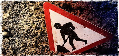 Construction sign shows man digging hole