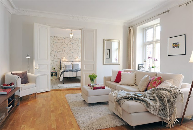 Alternative view of the living room where you can see a taupe armchairs and into the bedroom