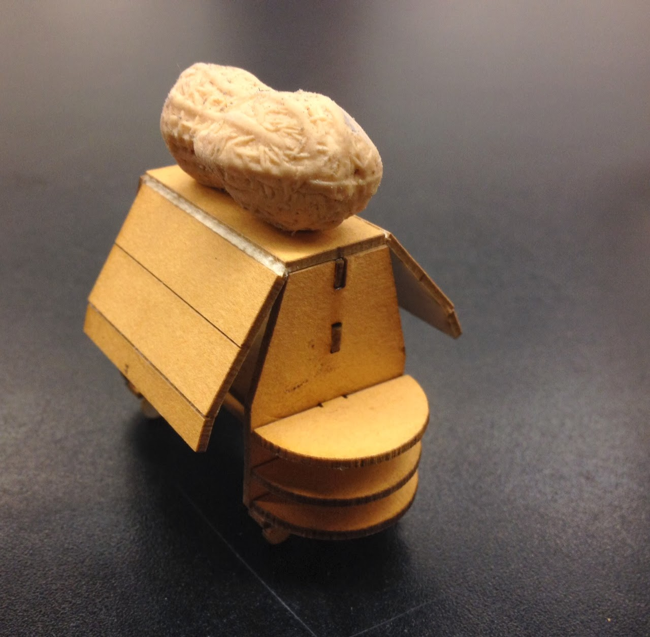 A wooden laser cut miniature kiosk model is assembled and has a peanut eraser on top for size reference.