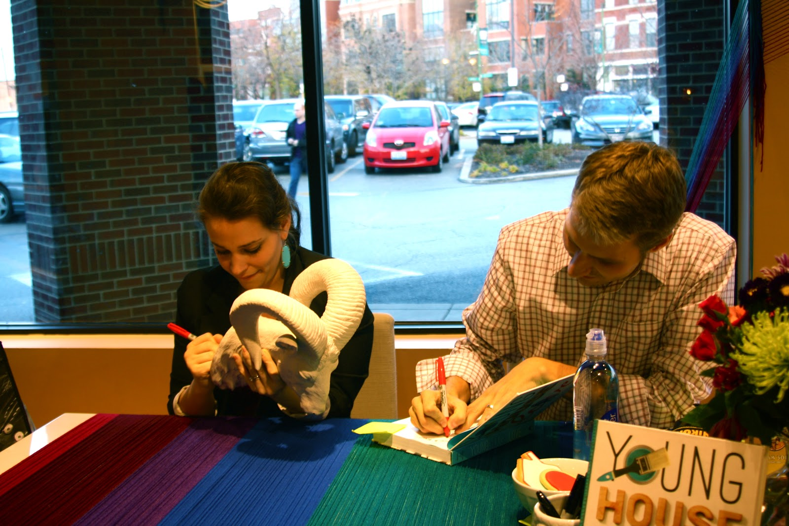 John and Sherry Petersik signing ceramic ram and Young House Love book