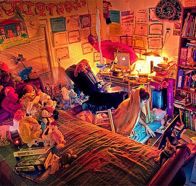 Ruberman Rodriguez picture of a warm, colourful, messy bedroom, with toys scattered, and child sitting on the floor wearing a blanket over their head, face illuminated by the laptop screen they are peering into intently.