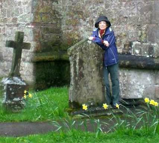 a photo of author Donna Fletcher Crow researching a story in Wales. She is standing among tombstones.