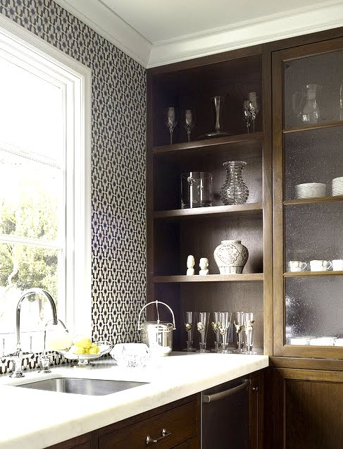 Close up of a kitchen with black and white Moroccan tiles, wood cabinets and white marble counter tops by House of Fifty