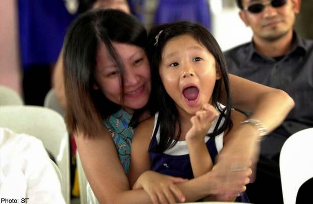 Mrs J. Yeo, 34, hugging her daughter as her child's name was pulled out of the ballot box at CHIJ St. Nicholas' Primary back in 2005.