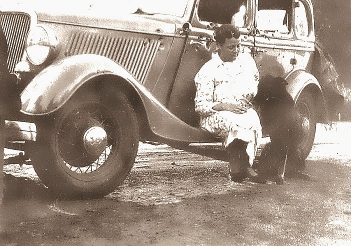 A poignant photo.  Ruth Warren with presumably her pup, & shot up car.