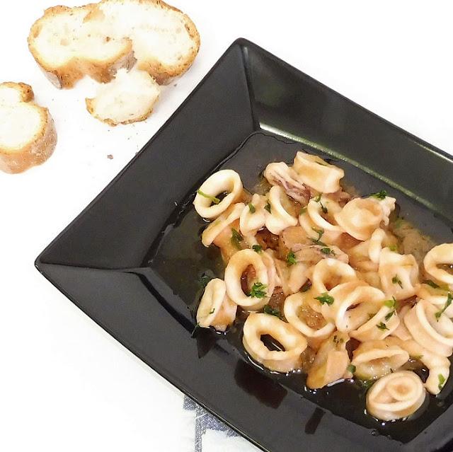 Plato de cazuela de calamares a la cerveza con trozos de pan sobre fondo blanco