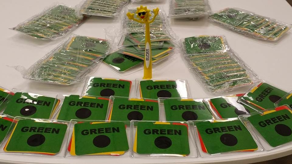 On a table-top: sets of green, yellow and red cards in clear plastic holders, the green card visible on top.