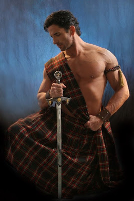 man in kilt with no shirt and holding a broad sword