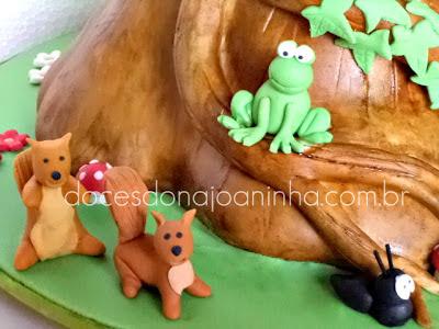 Bolo decorado Smurfs no formato de uma casinha tronco de árvore com cogumelos, esquilos, formiguinha e sapinho decorando a casinha tronco de árvore.