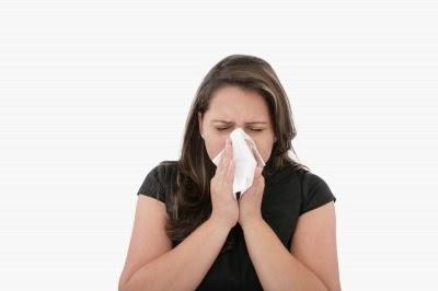 Mulher assoando o nariz