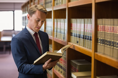 Smartly dressed man standing in a library studying law reports