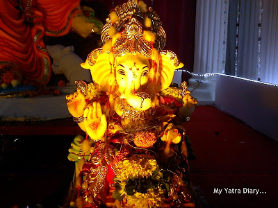 Ganpati idol  in Mumbai Pandal decorated with coconuts, fruits and flowers