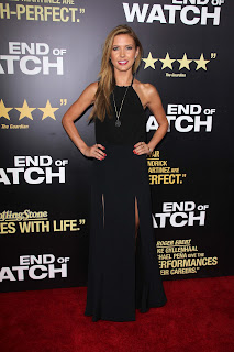 Audrina Patridge strikes a pose on a red carpet in a black dress